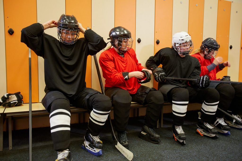Jääkiekkoilijat vaihtamassa varusteita ylleen